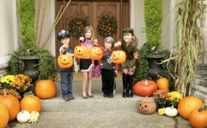 Four cute young kids dressed up in costumes on Halloween trick or treating